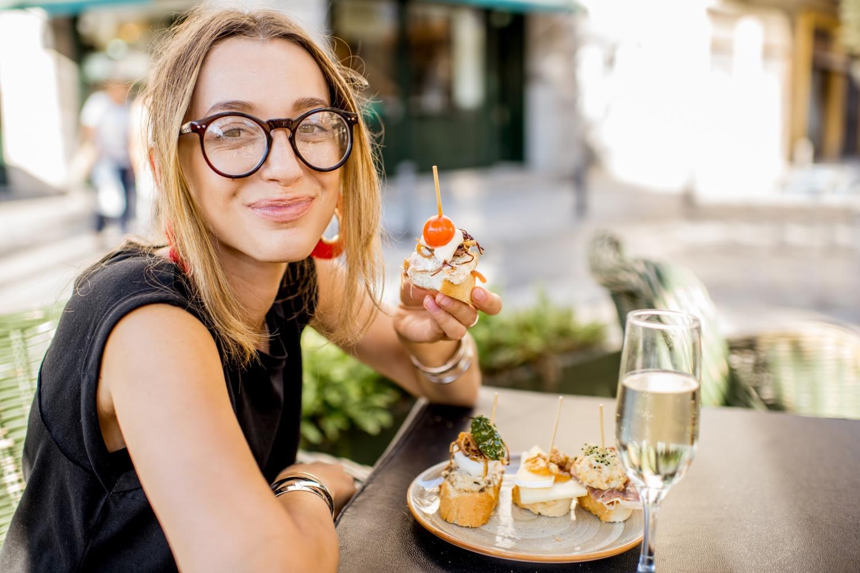 Woman eating spanish pinchos tapas at the bar outdoors