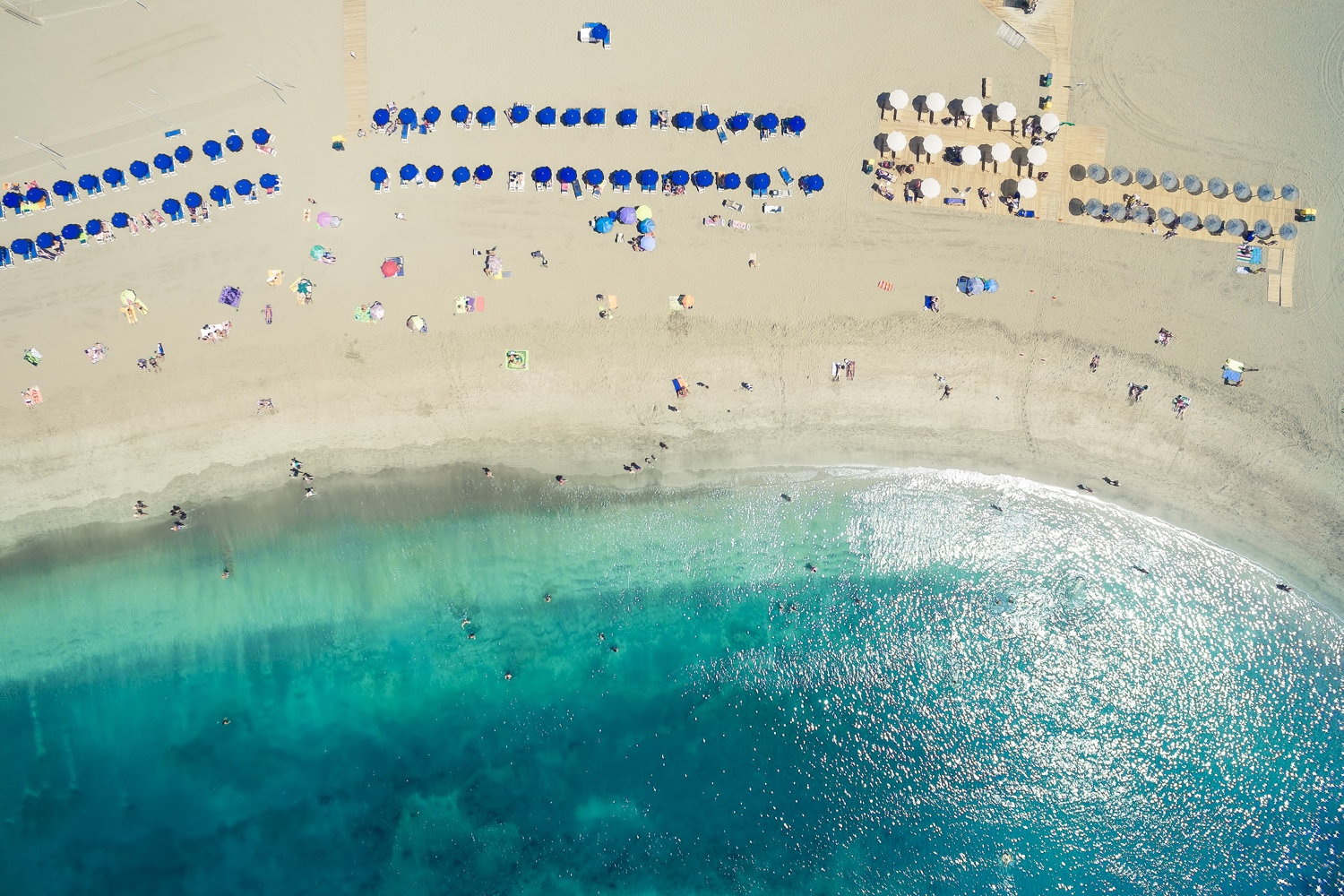 Drone aerial shot of people spending their holidays on beach and ocean in Adeje Playa de las Americas, Tenerife islands, Spain